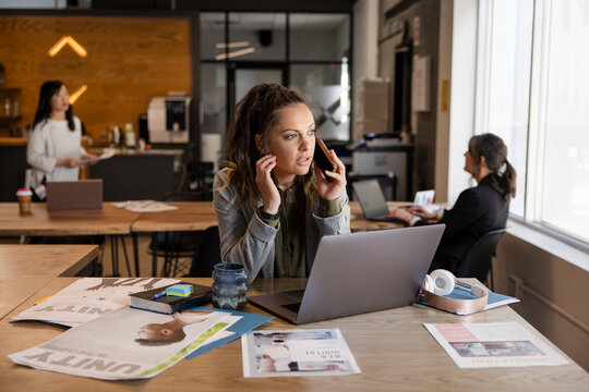 Creative businesswoman talking on smart phone at laptop