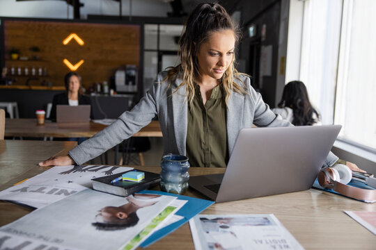 Creative businesswoman with proofs using laptop in coworking space