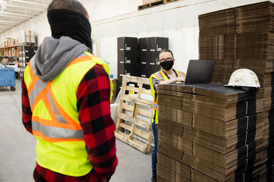 Warehouse workers in face masks talking