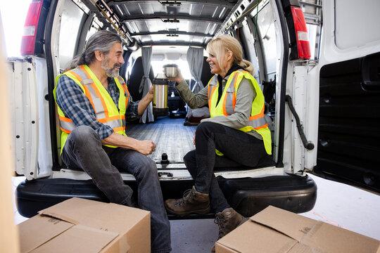 Happy warehouse workers enjoying coffee break at back of van