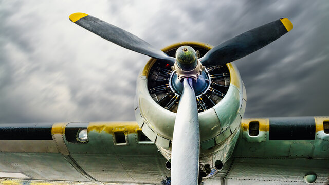 Vintage world war two bomber airplane wing, engine and propeller. Cloud filled sky. Room for copy text.