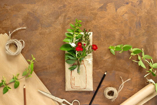 Gift wrapped in wrapping paper with bouquet of crimson roses and painted vase. Rolls of vintage packing paper, honeysuckle branches for decoration.