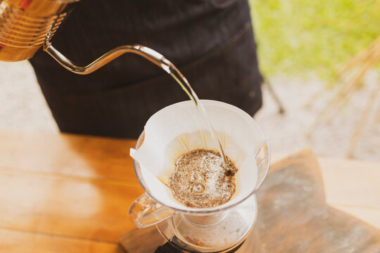 Barista making coffee pouring hot water on paper filter on top of glass coffee jar. Brazilian organic artisanal bakery small business concept.