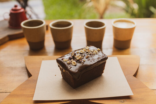 Natural organic chocolate brownie cake with nuts and chocolate cream on top., coffee cups out of focus on the background. Brazilian organic artisanal bakery mall business concept.