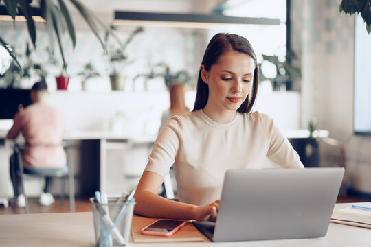 Young attractive businesswoman working on laptop in office