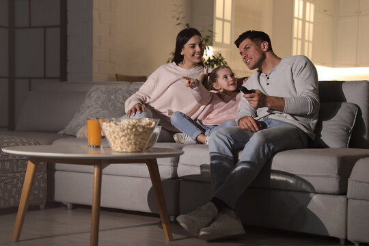 Family watching movie with popcorn on sofa at night