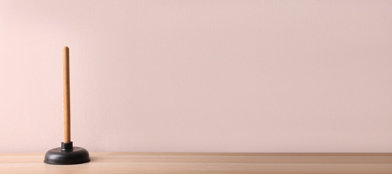 Plunger on wooden table against pink background. Space for text