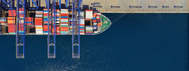 Obraz Aerial top down ultra wide photo of industrial container ship loading  - unloading colourful truck size containers with cranes in logistics terminal port - fototapety do salonu