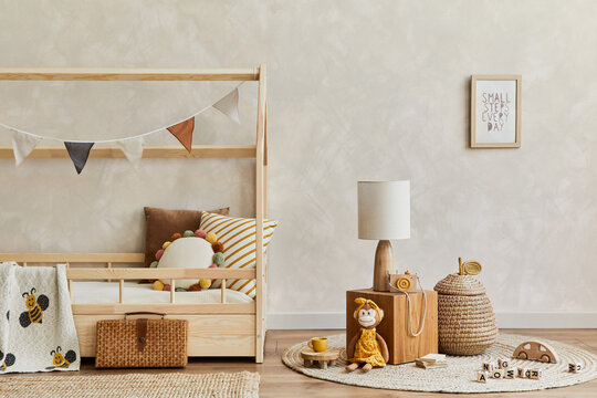 Stylish composition of cozy scandinavian child's room interior with wooden bed, plush and wooden toys and textile hanging decorations. Creative wall, carpet on the parquet floor. Copy space. Template.
