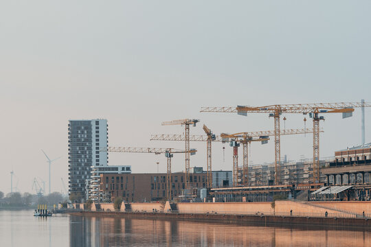 Cranes At Construction Site By River Against Sky In City