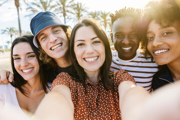 Fototapeta Group of happy multiracial people taking a selfie with mobile phone with back sunlight - Multiethnic friends in summer clothes having fun on holidays - Friendship and summer vacation concept obraz