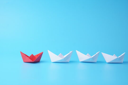 Leadership Concept Of Red Paper Ship Leading Among White