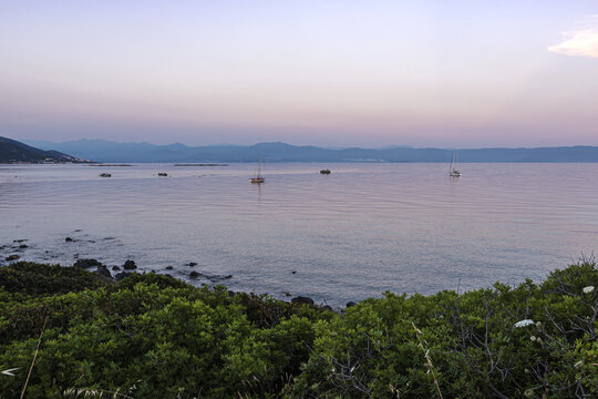 Fishing boats and yachts in the water of Ajaccio gulf under pinky sunset lights
