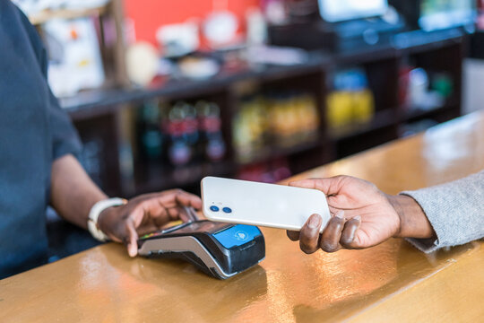 Crop buyer making payment with smartphone on terminal in bar