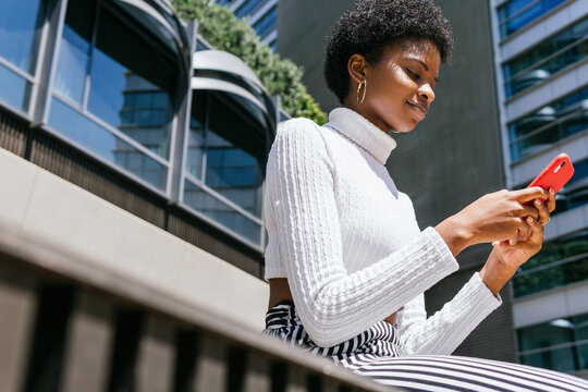 Trendy African American woman using smartphone on street