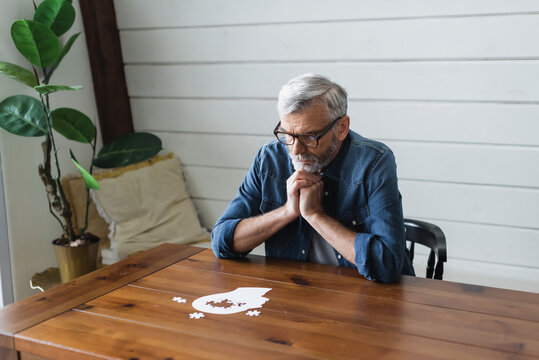 Pensive senior man looking at jigsaw on table