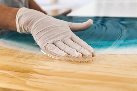 Female artist in protective gloves spreading white epoxy resin onto turquoise color