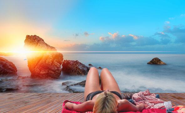 Woman sunbathing on beautiful cleopatra beach at sunset - Alanya