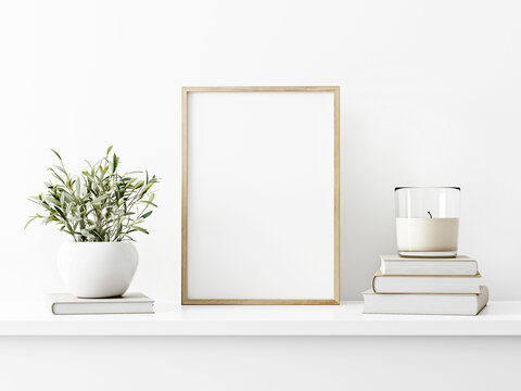 Vertical wooden frame mockup with green olive twigs in vase and candle on pile of books on white wall background. A4, A3, A size, 3d rendering, illustration