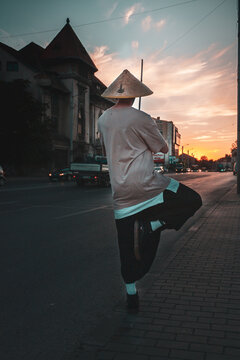 Rear View Of Man Walking On Footpath At Sunset