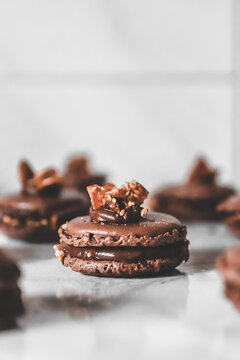 Close-up Of Chocolate Caramel Macarons On White Marble Table