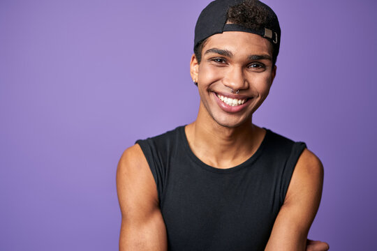 Portrait of smiling latino transgender man in black t-shirt and cap on purple background