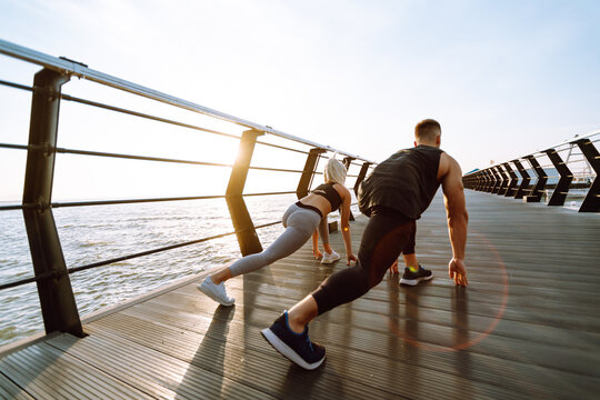 Young fitness couple is doing workout at the beach pier. Young man and woman doing exercises outdoors in the morning. Sport, Active life.