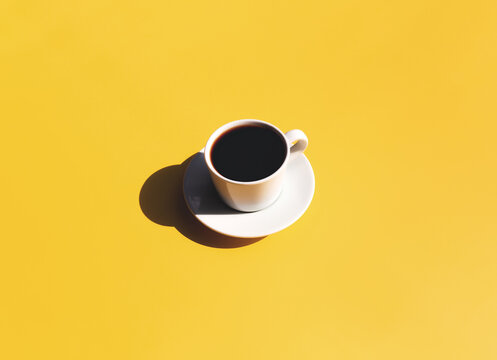 Cup and plate of coffee with shadow of sun on yellow beige terracotta background