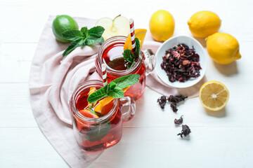 Mason jars of tasty ice tea with fruits on light wooden background