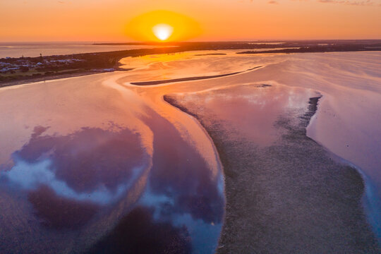 Aerial view of a dramatic sunset over islands and reflections in a coastal bay