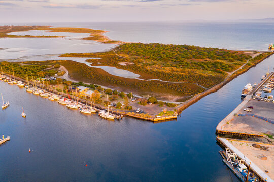 Aerial view of narrow channel joining a yacht harbour and a coastal bay.