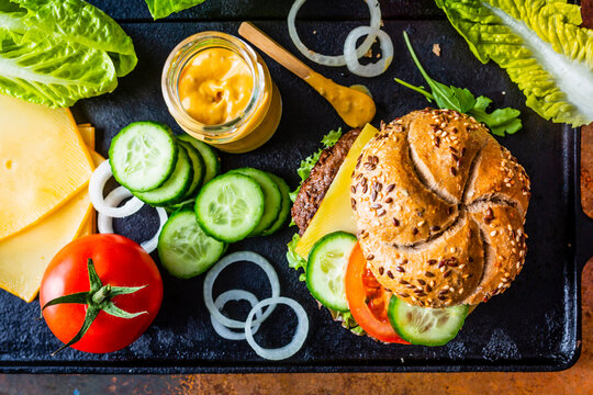Tasty grilled and glazed beef burger with lettuce, cheese and vegetables on vintage background.