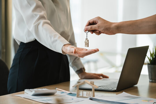 close up view hand of property realtor landlord giving a key house to buyer tenant at modern office