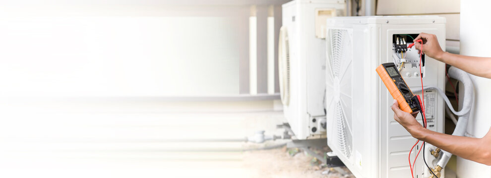 Air conditioner repairman using electricity meter to check air conditioner operation, maintenance concept