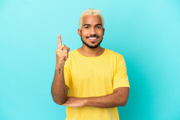 Obraz Young Colombian handsome man isolated on blue background happy and pointing up - fototapety do salonu