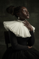 Fototapeta Close-up portrait of medieval African young woman in black vintage dress with big white collar posing isolated on dark green background. obraz