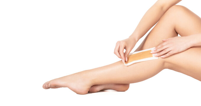 Beautician waxing female legs in spa center. Well-groomed woman legs after depilation isolated on white background. Waxing woman leg with wax strip at beauty spa. Close-up waxing woman leg in spa
