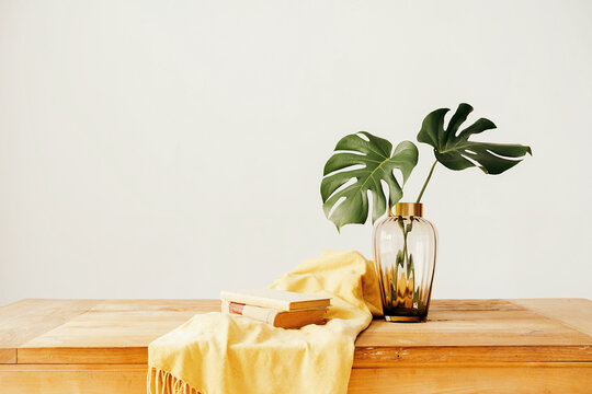 Books and vase with plants on table