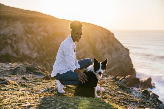 Black woman with dog on beach