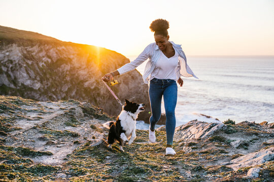 Black woman running with dog on beach