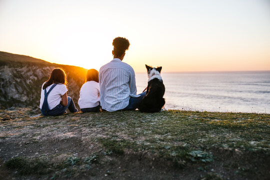 Woman with kids and dog resting on beach at sunset