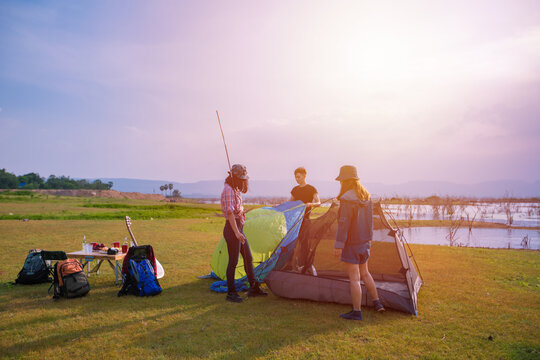 group of Asian friends tourist drinking and playing guitar together with happiness in Summer while having camping near lake at sunset