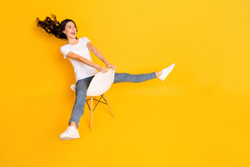 Full body profile side photo of attractive woman sit chair fly air look empty space isolated on shine yellow color background Wall mural