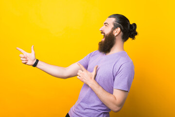 Obraz Happy excited bearded man pointing away at copy space with two fingers isolated over yellow background - fototapety do salonu