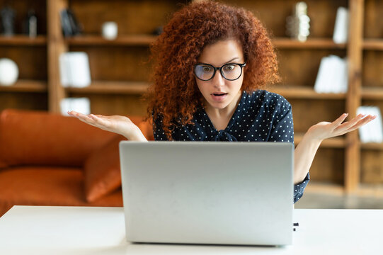 Puzzled and confused redhead female entrepreneur staring at the laptop screen, curly woman in shirt and eyewear looking at monitor with asking expression, misunderstanding what happened