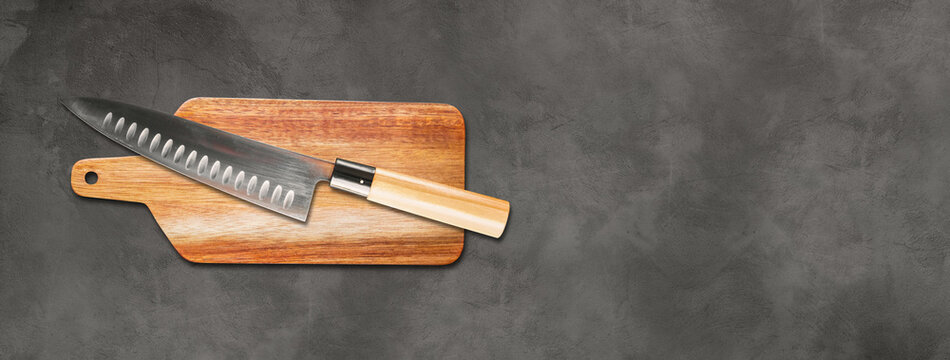 Traditional Japanese gyuto chief knife on a cutting board. Concrete background banner