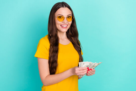 Photo of cute young lady count money wear eyewear yellow t-shirt isolated on vivid teal color background