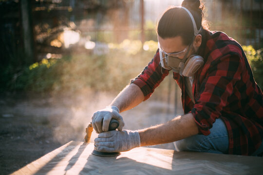 A male carpenter works with a wood grinder. Professional equipment and protective equipment.