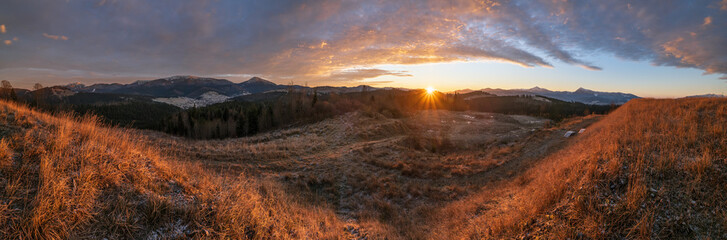 Picturesque sunrise above late autumn mountain countryside. Ukraine, Carpathian Mountains. Peaceful traveling, seasonal, nature and countryside beauty concept scene.