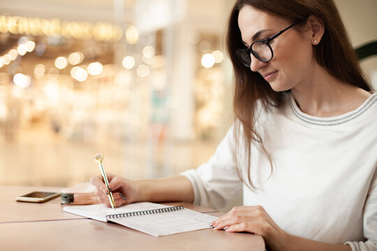 Young businesswoman in eyeglasses planning and writing down the daily schedule with in agenda